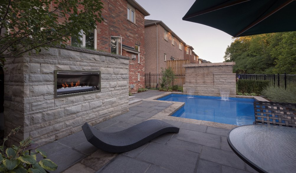 Contemporary outdoor fireplace poolside with granite patio