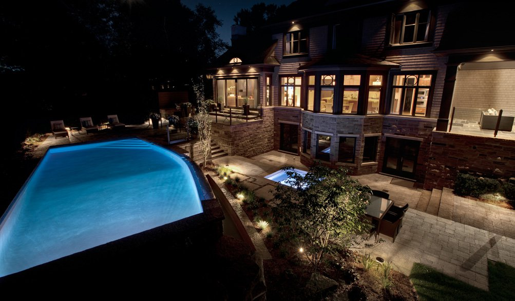 Custom home in oakville with concrete pool and dramatic landscape lighting design