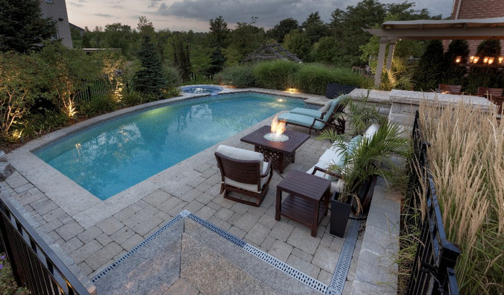 Dramatic outdoor living space with custom limestone pool and dramatic planting