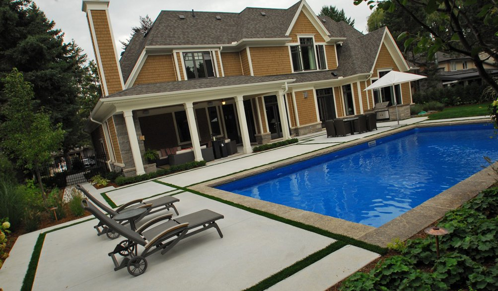 Transitional design example with contemporary landscape and a more traditional home