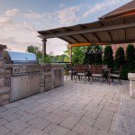 Outdoor kitchen with limestone bar paving stone patio and pergola sitting area